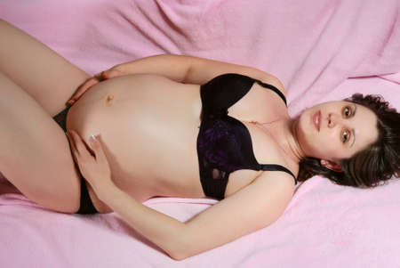 Pregnant woman with naked belly lying on a pink background. photo
