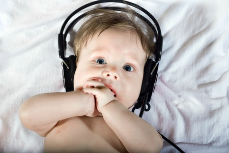 Portrait of beautiful baby listening to music on headphones.