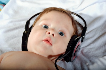 Portrait of a beautiful baby with headphones listening to music. photo