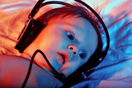 The small baby listening to music with headphones on tinted background. Stock Photo