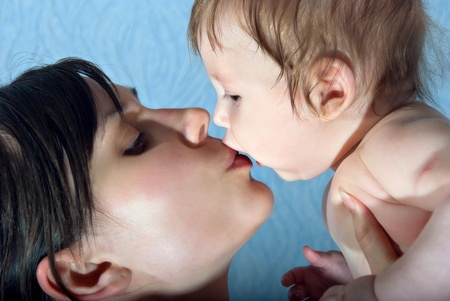 Happy mother kissing the baby holding him in her arms. photo