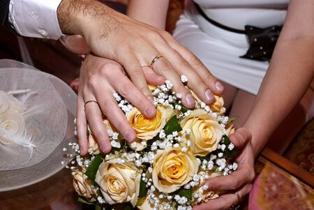 Wedding bouquet from white and pastel yellow roses, hands and rings. photo