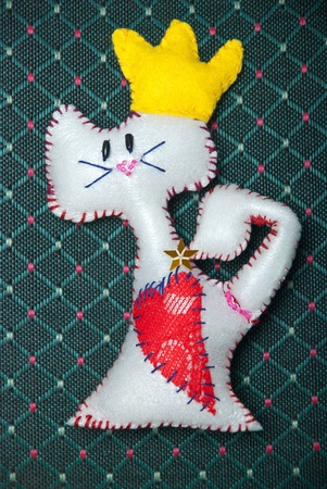 Cartoon cat with heart shape on the vintage textile background. photo