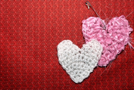 Two hearts on a red knitted textile background.