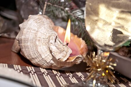 Decorative candle in a seashell. Focus on the shells. photo