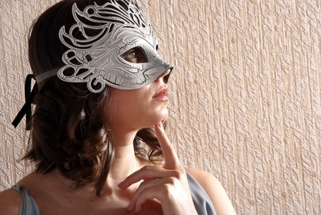 Cute girl in masquerade mask with a finger near the face. photo