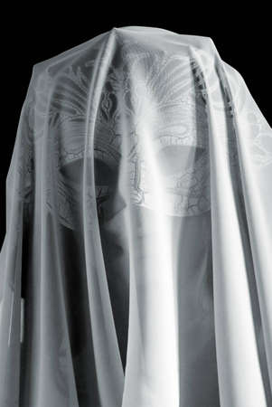 The mysterious girl in a mask with the face covered by the veil. Black and white photo photo