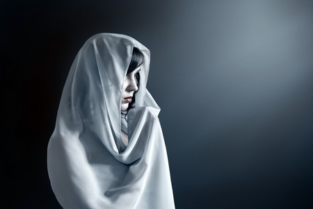 Young attractive woman in a veil prays on a dark background
