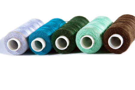 Five bobbins of colored thread on an isolated white background  photo