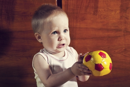 Funny boy with a soccer ball in his hands on an abstract background  photo