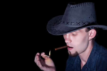 A young cowboy in a hat lights up a cigar on black background. photo