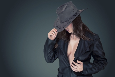 Sexy woman in a cowboy hat in a stylish coat and beautiful breasts  photo