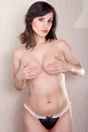 Attractive nude woman in black panties, covering her breast with hands. Studio shot. Stock Photo