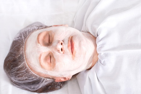Attractive woman with facial mask lies in spa salon  photo