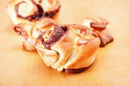 Closeup freshly homemade sweet rolls on a wooden table. Stock Photo