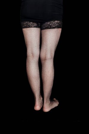 long sexy legs: Female long sexy legs in black stockings with space for text on black background. Stock Photo