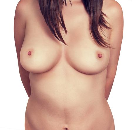 senos desnudos: Pecho desnudo de mujer de cerca sobre un fondo blanco.