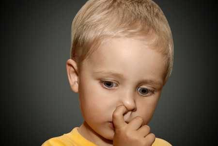 Young boy picking his nose. photo
