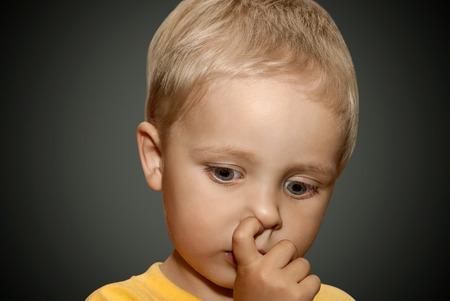 nose picking: Young boy picking his nose.
