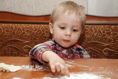Little funny boy in the kitchen engaged in cooking