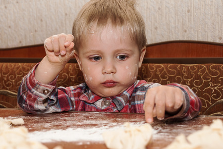 Little funny boy in the kitchen engaged in cooking photo