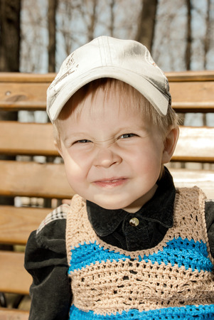 Portrait of little boy in cap outdoors.