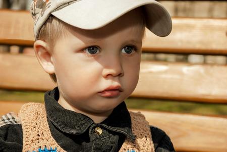 Portrait of little boy in cap outdoors.