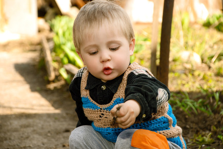 Little boy sitting in the garden playing ground. Stock Photo
