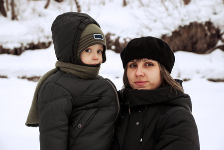 Mother with baby in the winter outdoors. Stock Photo