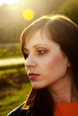 Beautiful female face outdoors back lit sunlight. Stock Photo