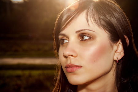 Beautiful female face outdoors back lit sunlight. Stock Photo
