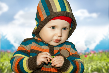 Little boy with leaf in hand knitted clothes outdoors.