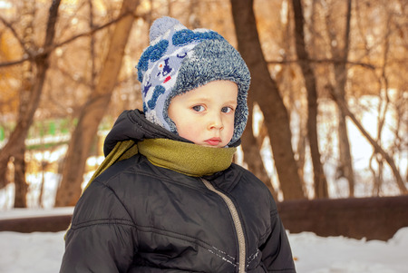 Portrait handsome little boy outdoors in winter photo
