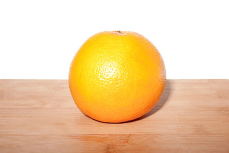 Ripe grapefruit on a wooden board with white back background.