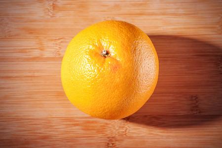 Ripe one grapefruit on wooden board.
