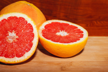 Slices of ripe red grapefruit on wooden board.