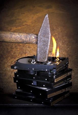 disk: symbolic data destruction theme showing the detail of a hammer on a stack of burning hard disks in front of rusty back