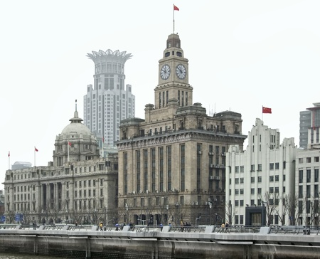 city view of the Bund, an area of the Huangpu District in Shanghai, a city in China,The buildings in the foreground from left to right are the HSBC building, the customs house and the bank of communications building