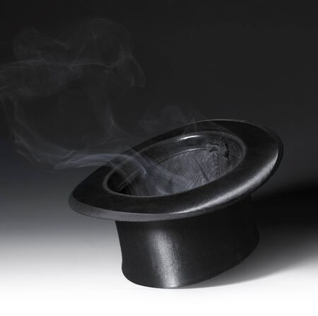 conjuring: magic scenery with a black top hat and some smoke in gradient back Stock Photo