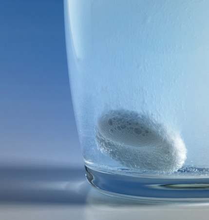 closeup studio shot of a dissolving fizzy tablet in a glass of water Stock Photo - 10838376
