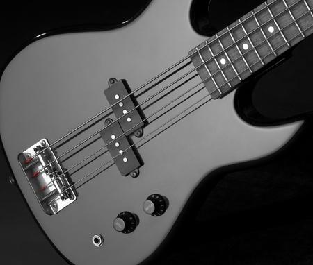 detail of a black bass guitar in dark back photo