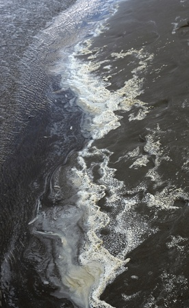 water damage: abstract pollution theme showing the edge of the water with dirty foam and dark sand Stock Photo