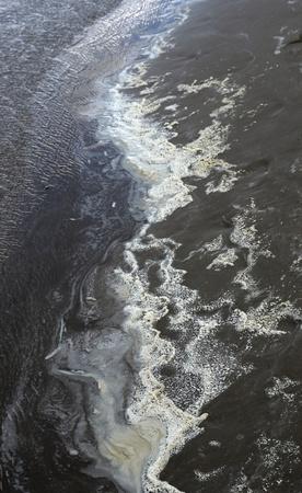 contaminacion del agua: tema de la contaminaci�n abstracto que muestra el borde del agua con espuma sucia y arena oscura Foto de archivo