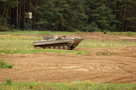 tracked: old tank of the Nationale Volksarmee in Germany, now used for a private tank driving school, while driving on earthy ground Stock Photo