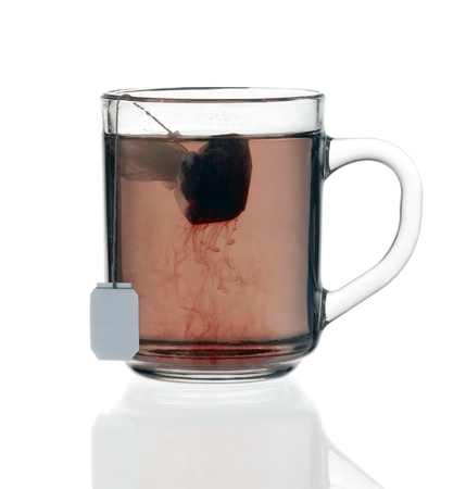 transparent glass teacup including reddish fluid with tea bag, on reflective groung isolated on white with clipping path Stock Photo - 10840303