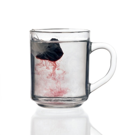 transparent glass teacup including reddish fluid with tea bag, on reflective groung isolated on white with clipping path Stock Photo - 10840308