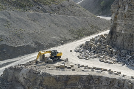 yellow stone pit digger after work in sunny ambiance, seen from above