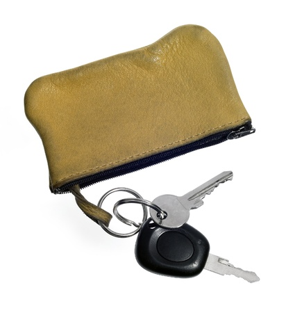 reachability: studio photography of some keys and light brown leather bag isolated on white