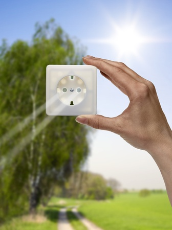 human energy: symbolic solar energy theme showing a idyllic outdoor scenery with human hand holding a electrical socket in front of the sun while sunbeams falling through