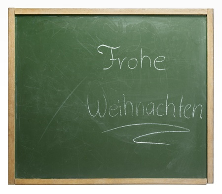 home schooling: old used blackboard with written Frohe Weihnachten on it. Studio photography in white back